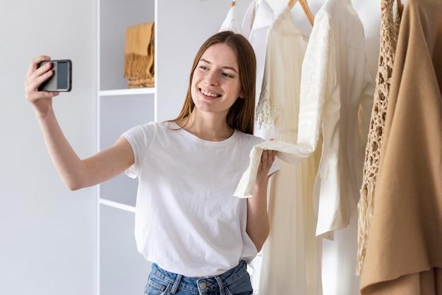 Blogger показывает свою одежду и использует смартфон