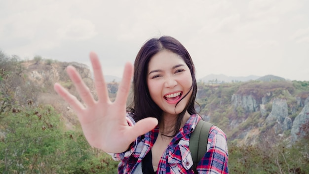Blogger азиатская рюкзаком женщина записывает видео на вершине горы