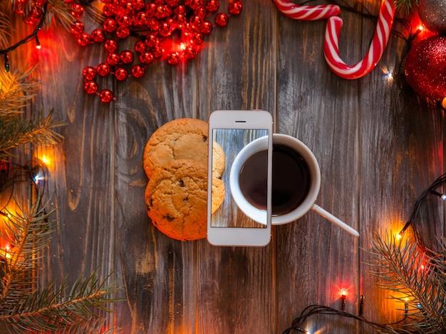 Концепция блогов и мобильной фотографии. рождественский и новогодний праздничный декор на деревянном фоне, сказочные огни и бусы, окружающие чашку кофе и шоколадное печенье.