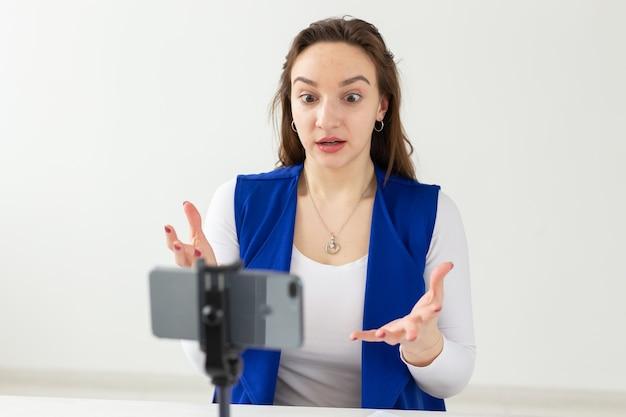 Концепция ведения блога и видеоблога - молодая женщина-блоггер разговаривает в камеру