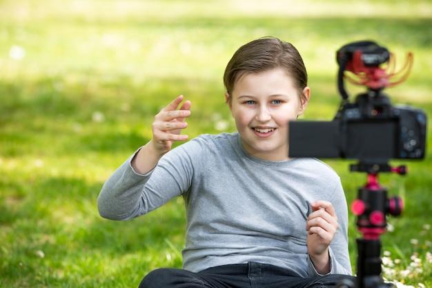 Концепция ведения блога и видеоблога, счастливый улыбающийся мальчик или блоггер с камерой, записывающей видеоблог в лесу за пределами леса