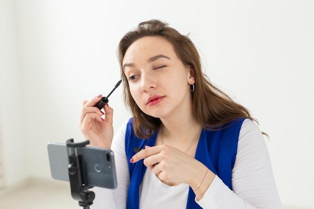 ブログ、放送、化粧品のコンセプト-美容ブロガーまたはビデオブロガーがマスカラを伝えて見せます。
