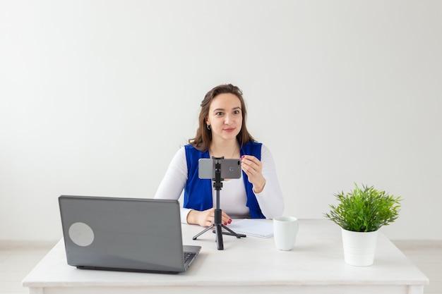 블로깅, 방송, 사람 개념 - 여성 블로거가 관중을 위해 카메라에 말하고 있습니다.