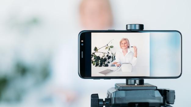 블로그 장비. 삼각대에 스마트폰입니다. 사진 및 비디오 촬영. 여성 뷰티 블로거