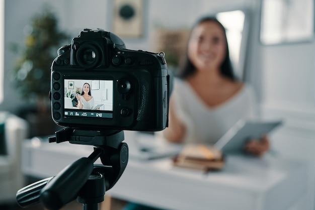 ブログは彼女の人生です。彼女のブログの新しいビデオを作成しながら身振りで示すと笑顔の美しい若い女性