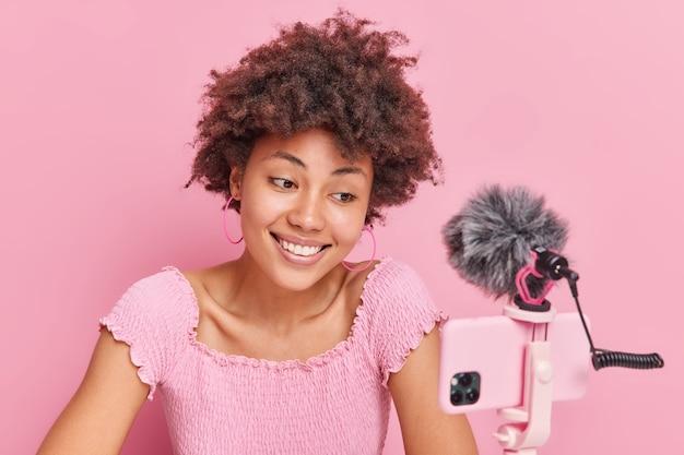 ブログのポッドキャスト録音とビデオストリーミングのコンセプト。笑顔のアフリカ系アメリカ人女性は、スマートフォンのカメラを見て自然な巻き毛を持っています