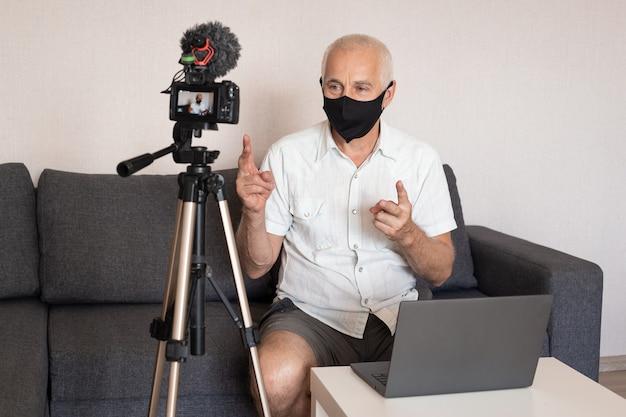 Блог, видеоблог и люди концепция - видеоблог с камерой, записывающий видеоблог старшего блоггера-мужчину в маске дома