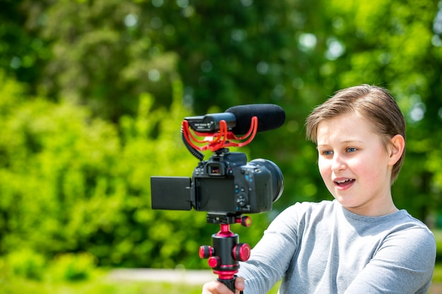 Blogging and vlogging concept, happy smiling boy or blogger with camera recording video blog in outside forest