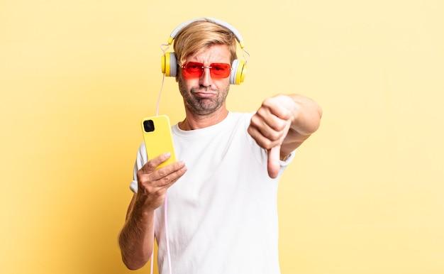 金髪の成人男性がクロスを感じ、ヘッドフォンで親指を下に見せます