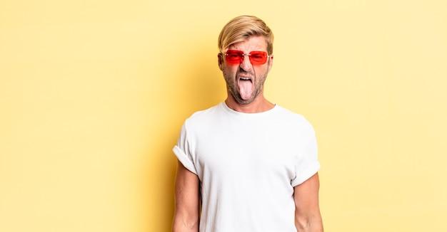 Блондинка взрослый мужчина чувствует отвращение и раздражение, высовывает язык и носит солнцезащитные очки