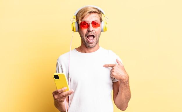 幸せを感じ、ヘッドフォンで興奮して自分を指している金髪の成人男性