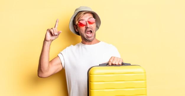 아이디어를 실현한 후 행복하고 흥분된 천재처럼 느끼는 금발의 성인 남자. 여행자 개념