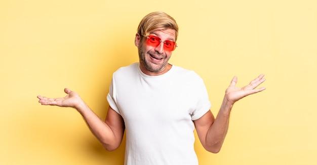 금발의 성인 남자는 어리둥절하고 혼란스럽고 의심하고 선글라스를 끼고 있습니다.