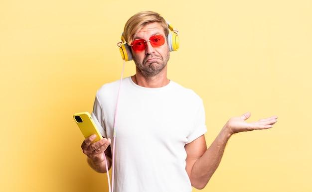 困惑し、混乱し、ヘッドフォンで疑っている金髪の成人男性