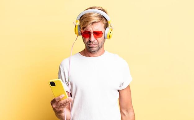 悲しい、動揺または怒りを感じ、ヘッドフォンで横を向いている金髪の成人男性