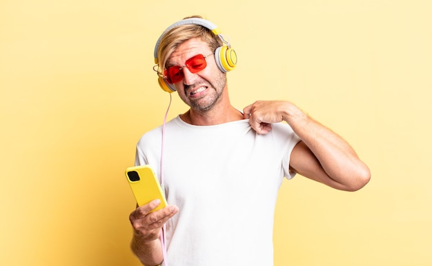 Blond adult man feeling stressed, anxious, tired and frustrated with headphones