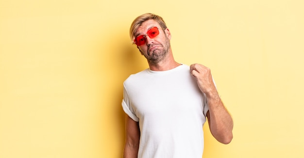 Blond adult man looking arrogant, successful, positive and proud and wearing sunglasses