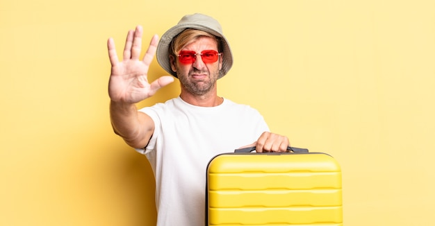 오픈 손바닥 중지 제스처를 보여주는 심각한 찾고 금발 성인 남자. 여행자 개념