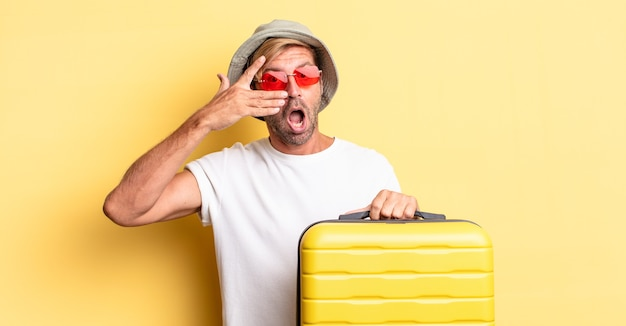 手で顔を覆って、ショックを受けたり、怖がったり、恐怖を感じたりする金髪の成人男性。旅行者のコンセプト