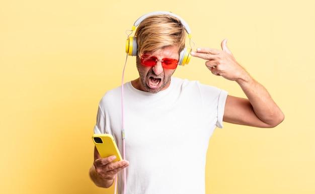 不幸でストレスを感じている金髪の成人男性、ヘッドフォンで銃のサインを作る自殺ジェスチャー
