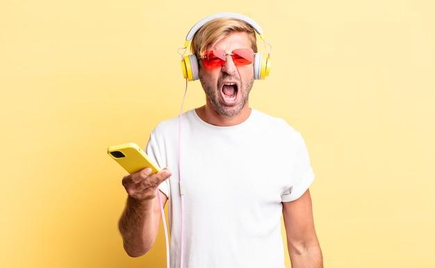 ヘッドホンで非常に怒っているように見える、積極的に叫んでいる金髪の成人男性