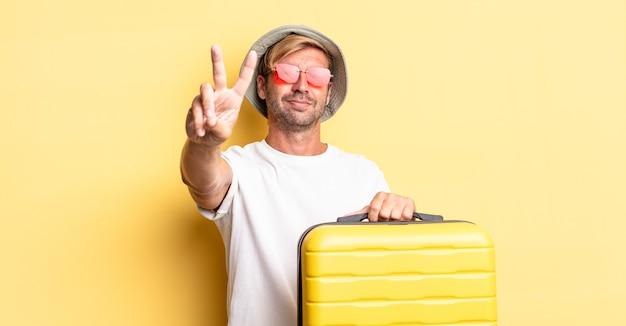 금발의 성인 남자는 미소를 짓고 친절하게 보이고 2번을 보여줍니다. 여행자 개념