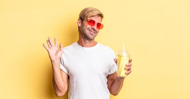 幸せに笑って、手を振って、ミルクセーキであなたを歓迎し、挨拶する金髪の成人男性