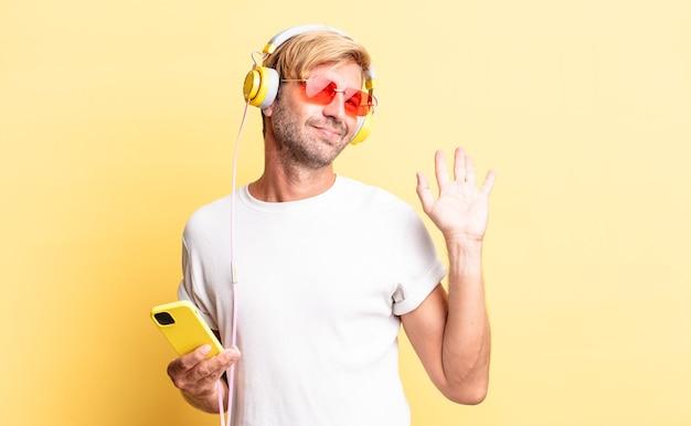 幸せに笑って、手を振って、ヘッドフォンであなたを歓迎し、挨拶する金髪の成人男性