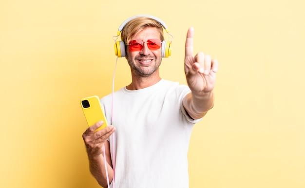 誇らしげにそして自信を持って笑顔の金髪の成人男性がヘッドフォンでナンバーワンを作る
