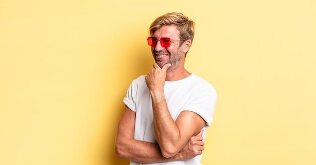 턱에 손을 대고 선글라스를 끼고 행복하고 자신감 있는 표정으로 웃고 있는 금발의 성인 남자
