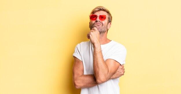 금발의 성인 남자가 생각하고 의심스럽고 혼란스러워하며 선글라스를 끼고 있습니다.