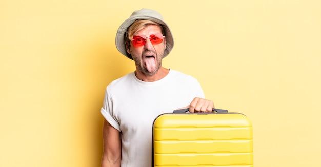 陽気で反抗的な態度、冗談を言ったり、舌を突き出したりする金髪の成人男性。旅行者のコンセプト