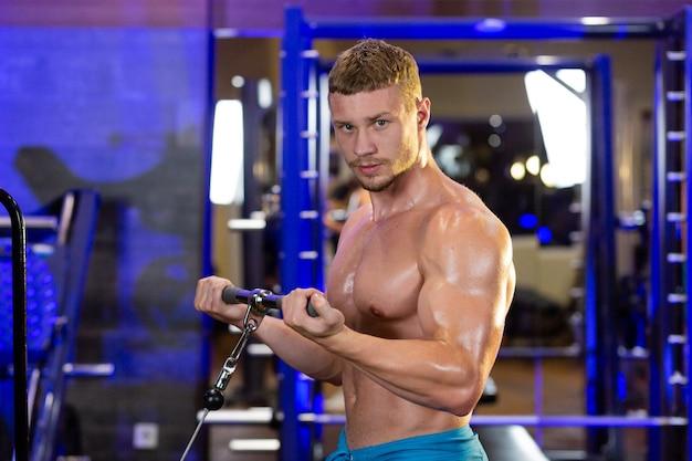 Блондинка спортсмен выполняет фитнес-упражнения в тренажерном зале