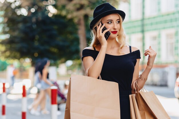 Blond attractive girl in a hat after shopping in the rays of the summer sun with phone