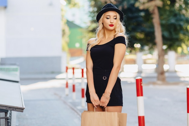 Blond attractive girl in a hat after shopping in the rays of the summer sun