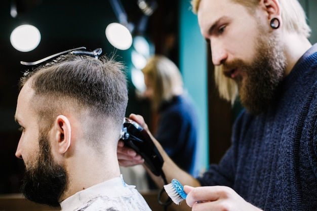 Blond bearded barder makes fade on man's hair attentively