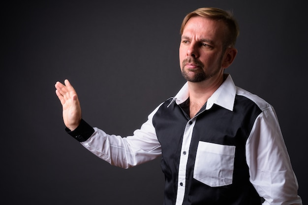 Blond bearded businessman with goatee against gray wall