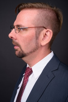 Blond bearded businessman with goatee on gray