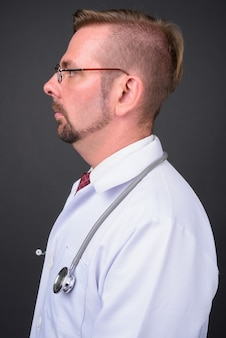 Blond bearded man doctor with goatee on gray