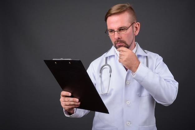 灰色のヤギひげを持つ金髪のひげを生やした男の医者