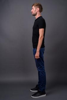 灰色の黒いシャツを着ている金髪のひげを生やした男