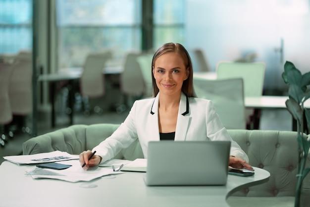 Блондинка красивая бизнесвумен, работа с документами, сидя перед ноутбуком в белом официальном костюме.