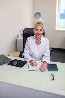 彼女のオフィスのテーブルに座っている白いローブを着ている金髪の美しい医者