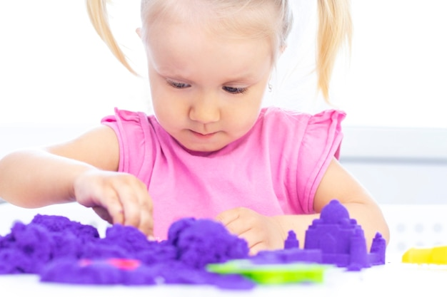 Blond beautiful girl smiles and plays with purple sand on a white table.