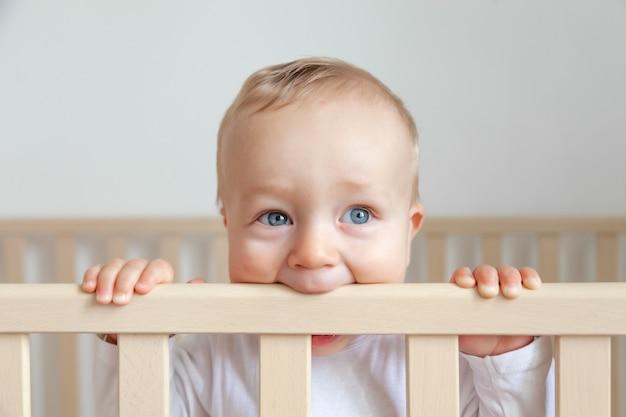 白いインテリアの背景に木製のベッドのヘッドボードをかむ白いボディースーツの青い目の小さな赤ちゃんの金髪の美しい肖像画