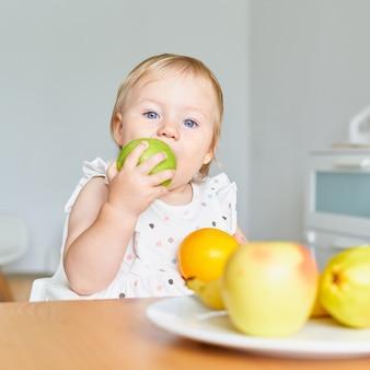 Светловолосый голубоглазый малыш кусает зеленое яблоко и смотрит в камеру, полную фруктов