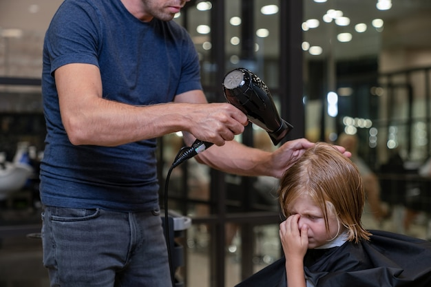 Blond boy in a beauty studio blow-dry his hair and do styling