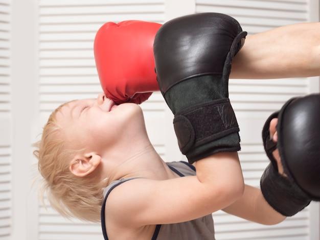 赤い手袋をはめた手でボクシングをする金髪の少年。顔を吹く