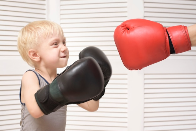 Blond boy boxing with hand in red glove