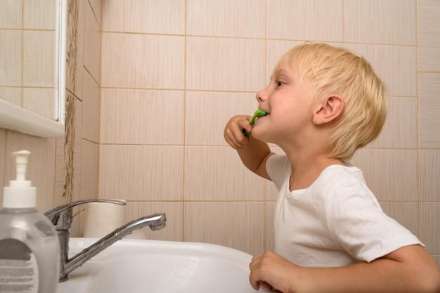 Blond boy brushes his teeth in the bathroom
